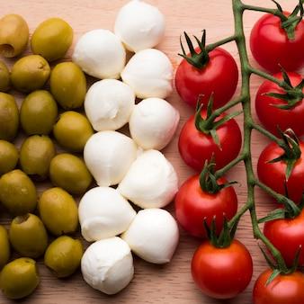Delicioso queso mozzarella; tomates rojos frescos y aceitunas mojadas en mesa de madera