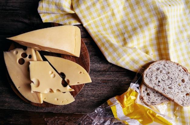 Delicioso queso sobre tabla de madera y pan