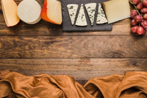 Delicioso queso y uvas dispuestas en una fila en mesa de madera con tela marrón