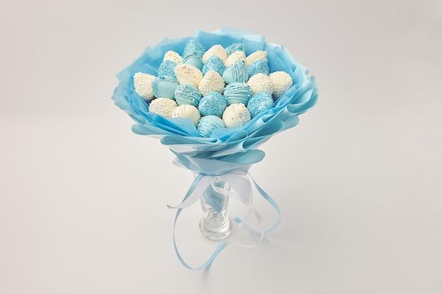 Delicioso ramo de fresas cubiertas de chocolate blanco y azul sobre un fondo blanco.