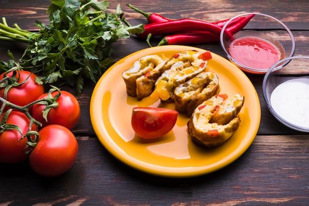 Delicioso rollo en plato entre verduras y salsas.