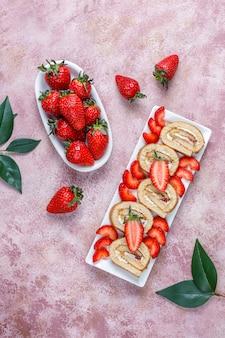 Delicioso rollo de tarta de fresas con fresas frescas, vista superior
