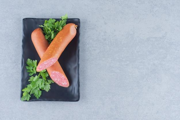Delicioso salami fresco en placa negra sobre fondo gris.