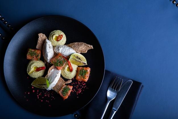 Delicioso salmón con paté y hummus en restaurante. saludable comida exclusiva en primer plato grande negro
