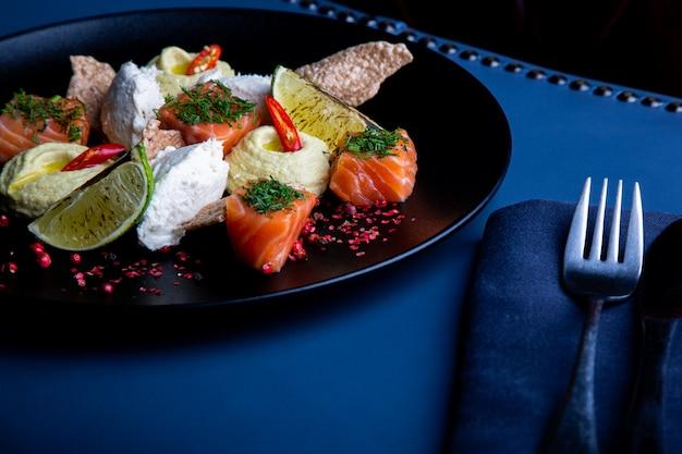 Delicioso salmón con paté y hummus en el restaurante. saludable comida exclusiva en primer plato grande negro