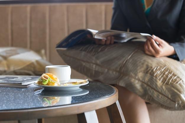 Delicioso sándwich y café en un plato en la mesa