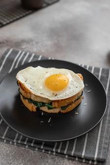 Delicioso sándwich de desayuno con huevo frito, espinacas y queso en un plato oscuro. de cerca