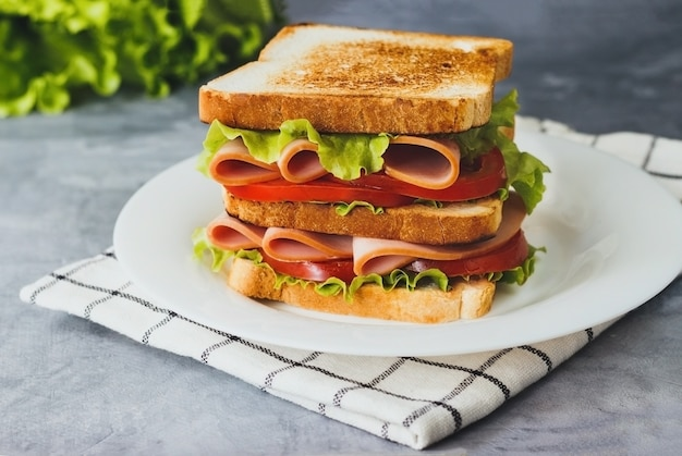 Delicioso sándwich con ensalada de jamón jamón y tomates sobre fondo gris