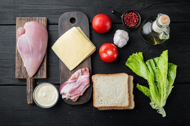 Delicioso sándwich con ingredientes de pan tostado, sobre mesa de madera negra, vista superior