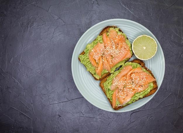 Delicioso sándwich con pan de centeno, aguacate y salmón snack gourmet