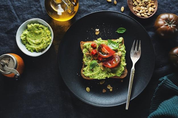 Delicioso sándwich de pan integral con puré de aguacate y tomates