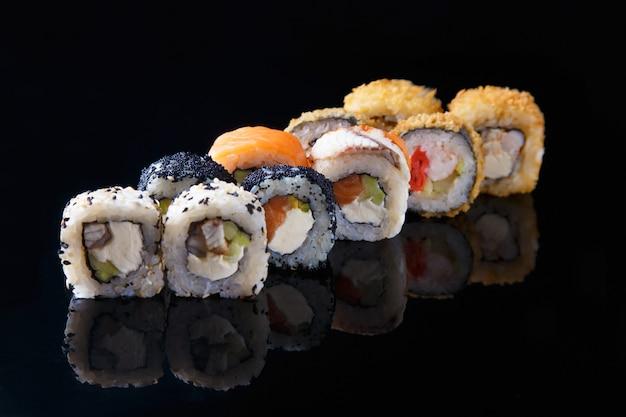 Delicioso set de sushi roll con pescado sobre un fondo negro con reflexión menú y restaurante