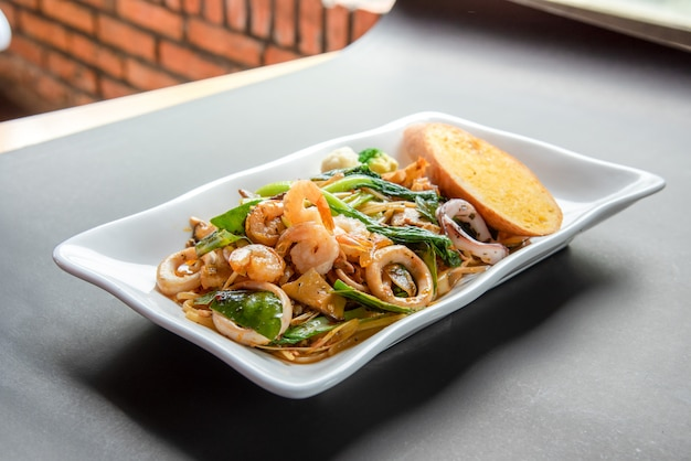 Delicioso spaghetti phut khi mao, espagueti de mariscos picante en plato blanco moderno