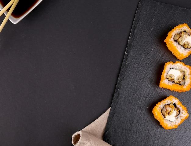 Delicioso sushi en plato negro