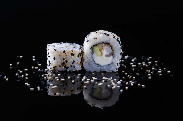 Delicioso sushi roll con pescado y sésamo sobre un fondo negro con reflexión menú y restaurante