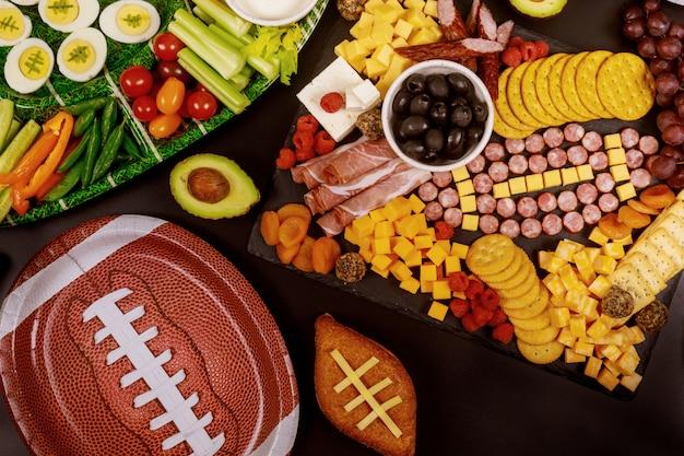 Delicioso tablero de charcutería y verduras con salsa para el juego del super bowl