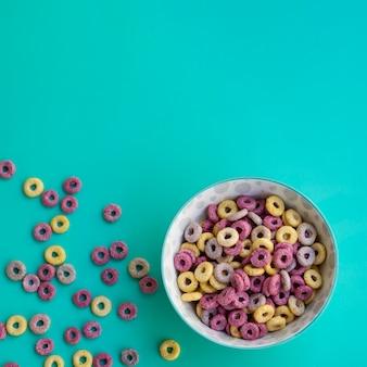 Delicioso tazón de cereales sobre fondo azul.