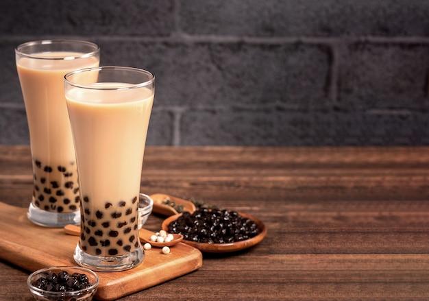 Delicioso té con leche de burbujas con bola de perlas de tapioca en vidrio sobre mesa de madera