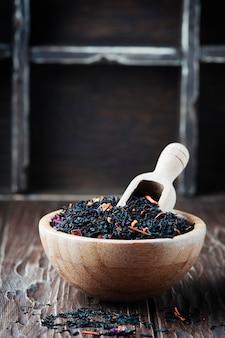Delicioso té negro con pétalos en la mesa de madera