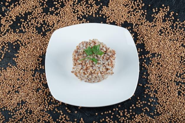 Delicioso trigo sarraceno con verduras en un plato blanco.
