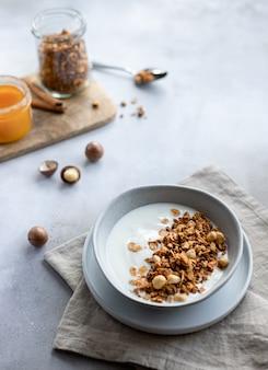 Delicioso yogurt con granola, nueces y miel en un tazón de desayuno saludable, snack gris hormigón fondo horizontal copia espacio