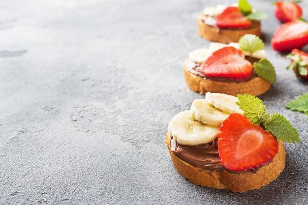 Deliciosos bocadillos con turrón de chocolate, fresa y plátano.