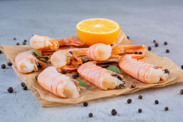 Deliciosos camarones con rodajas de limón y pimienta en papel vegetal