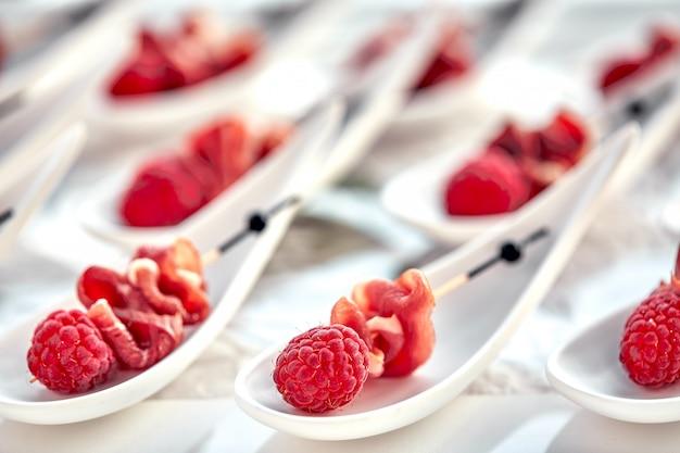 Deliciosos canapés hamon con frambuesas. concepto de comida, restaurante, catering, menú.