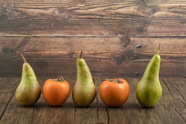 Deliciosos caquis fuyu y peras maduras sobre superficie de madera