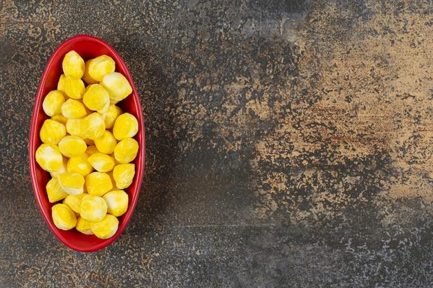 Deliciosos caramelos amarillos en tazón de fuente rojo.