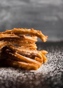 Deliciosos churros de primer plano sobre una mesa con azúcar borrosa