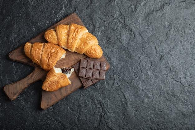 Deliciosos croissants con deliciosas barras de chocolate sobre una tabla de madera.