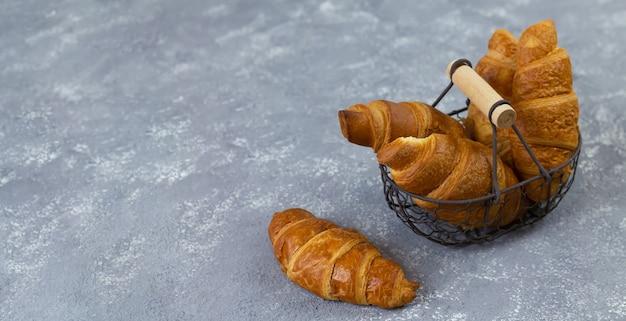 Deliciosos croissants frescos en la canasta de metal sobre la mesa de piedra gris, espacio de copia
