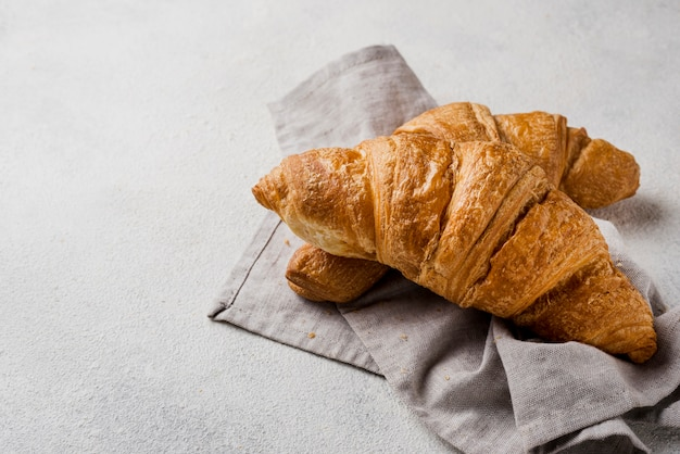Deliciosos croissants de vista frontal sobre tela de cocina