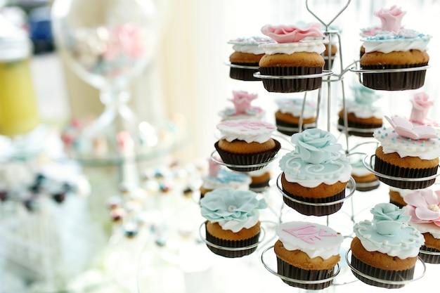 Deliciosos cupcakes con rosas de color rosa y azul glaseado puestos en titulares