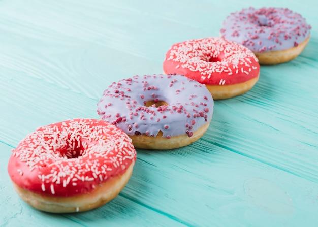 Deliciosos donuts dispuestos en una fila en la mesa de madera
