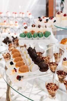 Deliciosos dulces en el buffet de dulces de boda con postres, cupcakes, tiramisú y galletas.
