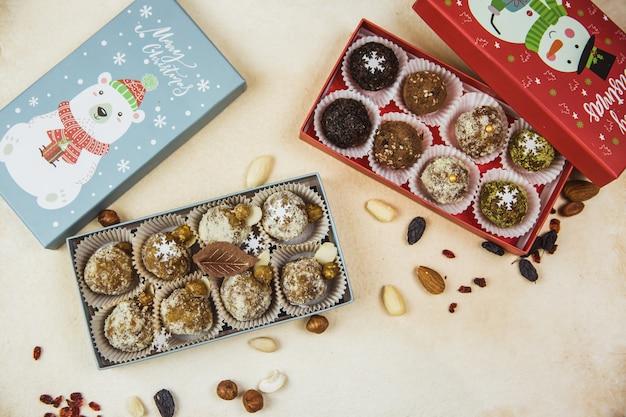 Deliciosos dulces crudos en porciones orgánicos caseros apilados en cajas de regalo de navidad