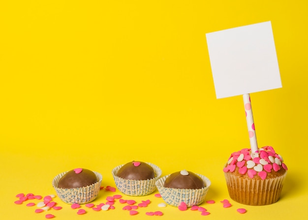 Deliciosos dulces dulces y pastel con papel sobre palo.