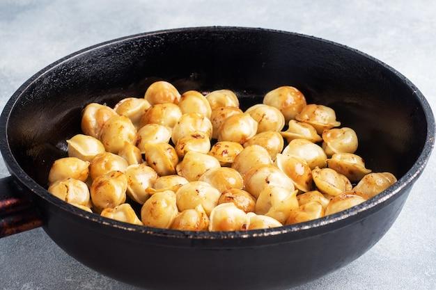 Deliciosos dumplings fritos con carne en una sartén.