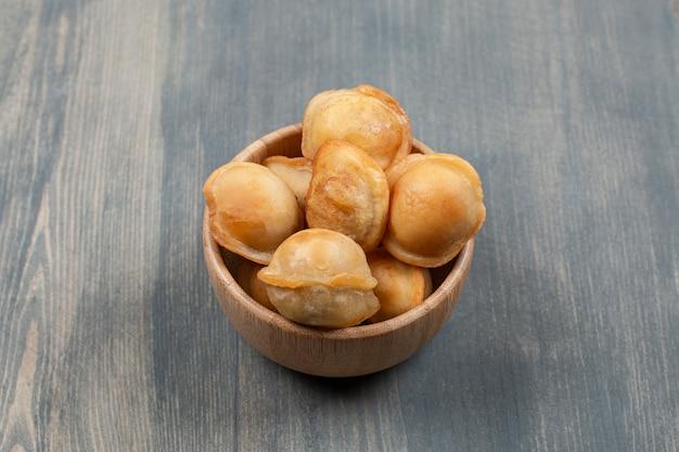 Deliciosos dumplings fritos en un cuenco de madera
