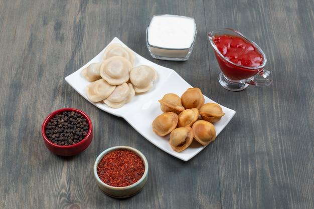 Deliciosos dumplings fritos y hervidos en una placa blanca.