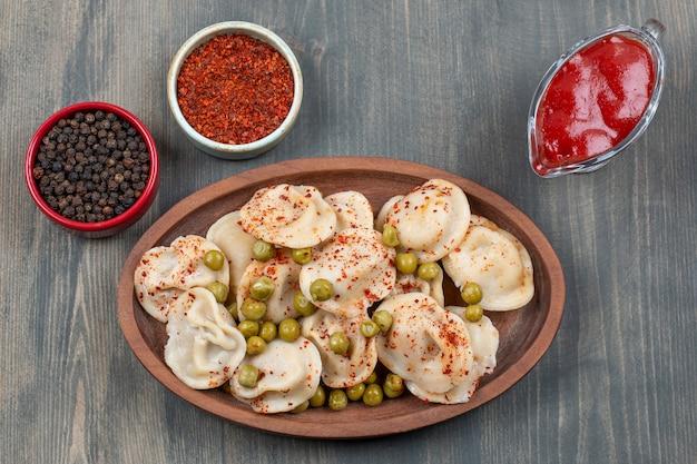 Deliciosos dumplings con guisantes y pimiento rojo
