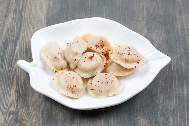 Deliciosos dumplings con pimiento rojo en una placa blanca.