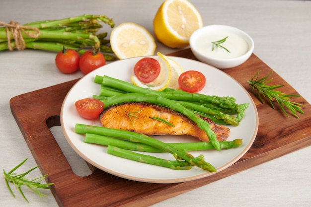 Deliciosos espárragos verdes y salmón ahumado en rodajas en un plato rústico