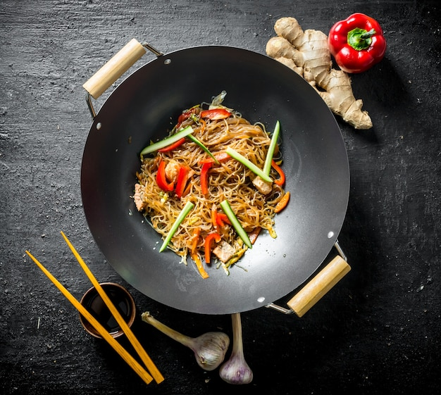 Deliciosos fideos de celofán en una sartén wok con palillos. en mesa rústica negra