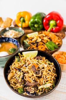 Deliciosos fideos y sopa con pimientos en mesa