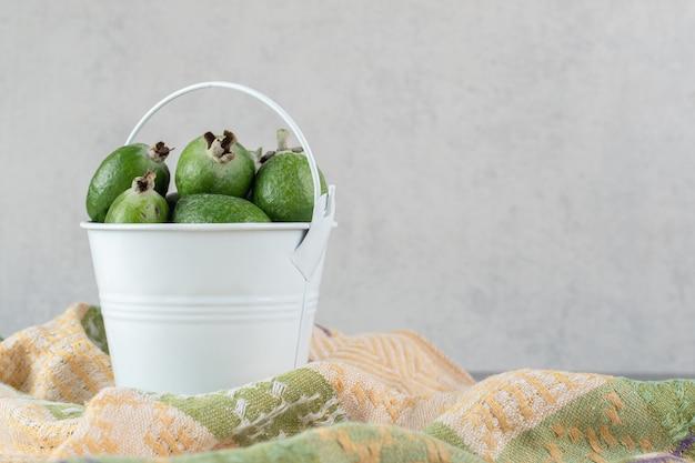 Deliciosos frutos de feijoa en balde blanco. foto de alta calidad