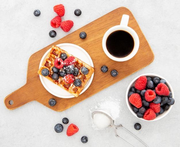 Deliciosos gofres dulces y café sobre tabla de madera