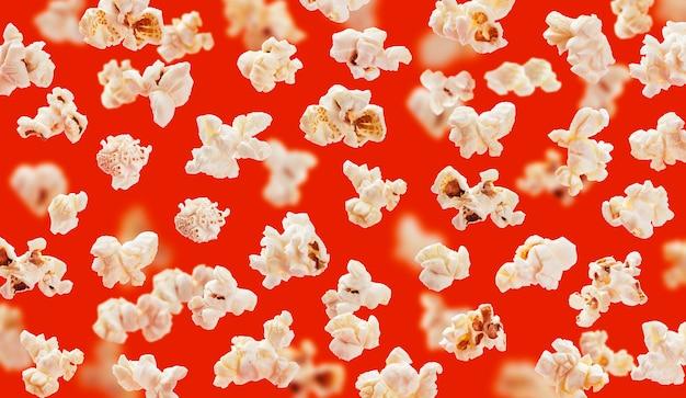 Deliciosos granos de palomitas de maíz closeup sobre fondo rojo.